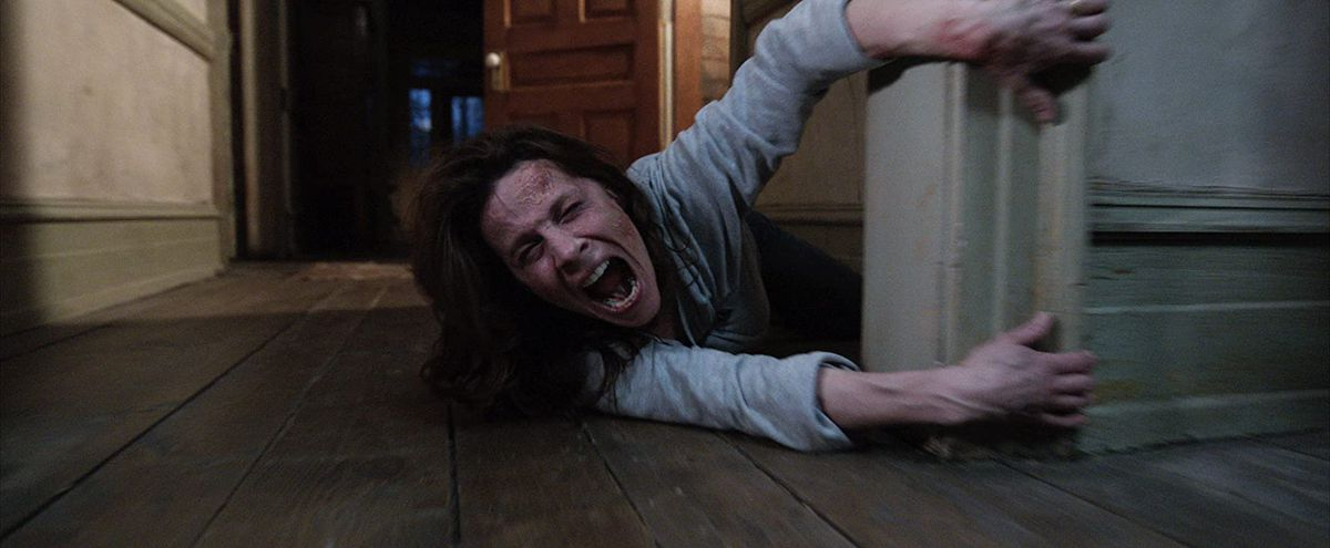A woman holds onto a door frame as she's dragged away