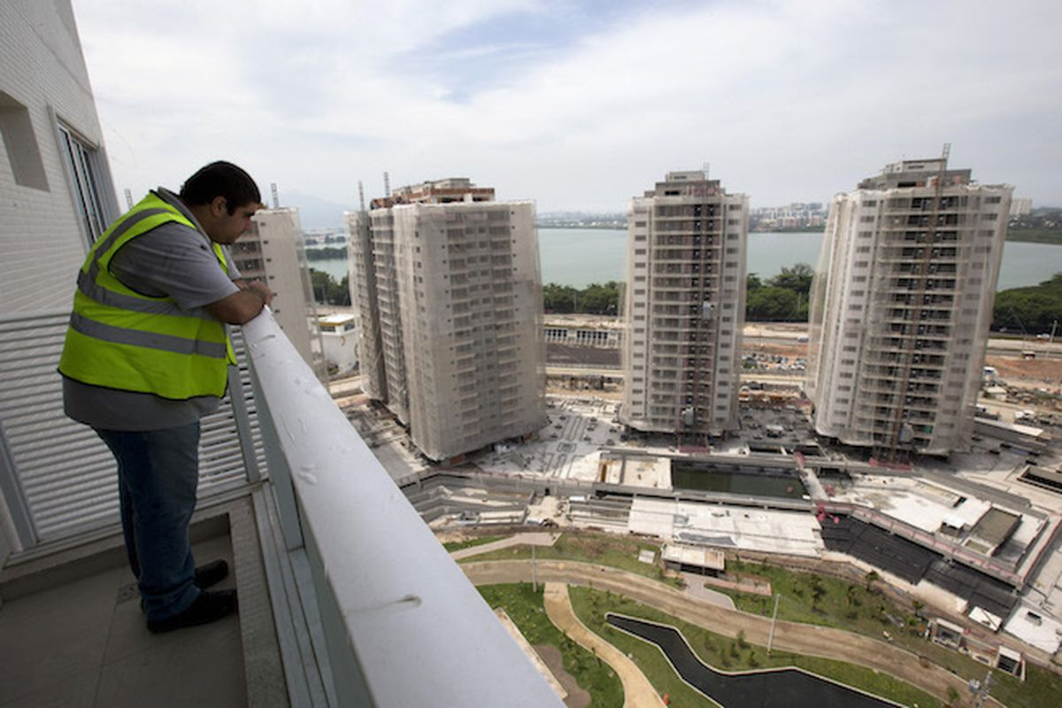 A worker stands on the balcony of an apartment inside the Rio 2016 Olympic Games athletes village in Rio de Janeiro, Brazil. The Ilha Pura towers, set to become private housing after the games, has struggled with presales. (AP Photo/Silvia Izquierdo