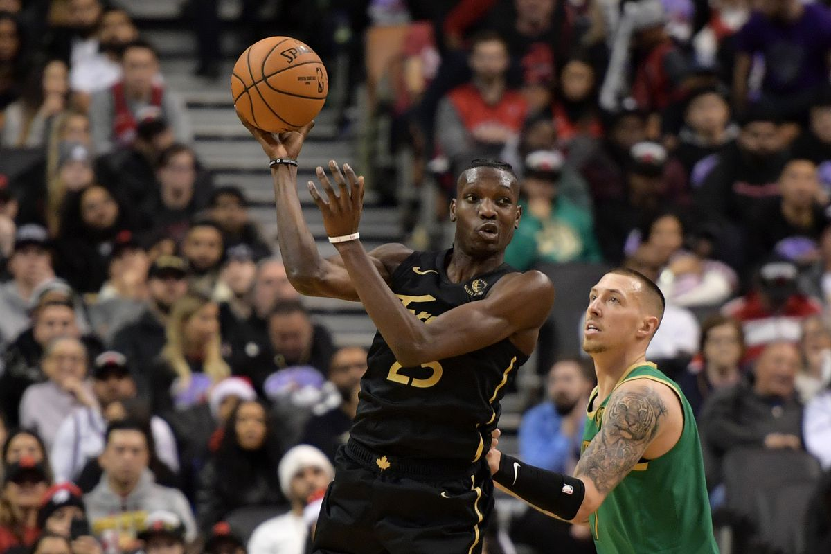 Toronto Raptors forward Chris Boucher passes the ball away from Boston Celtics forward Daniel Theis  in the second half at Scotiabank Arena.