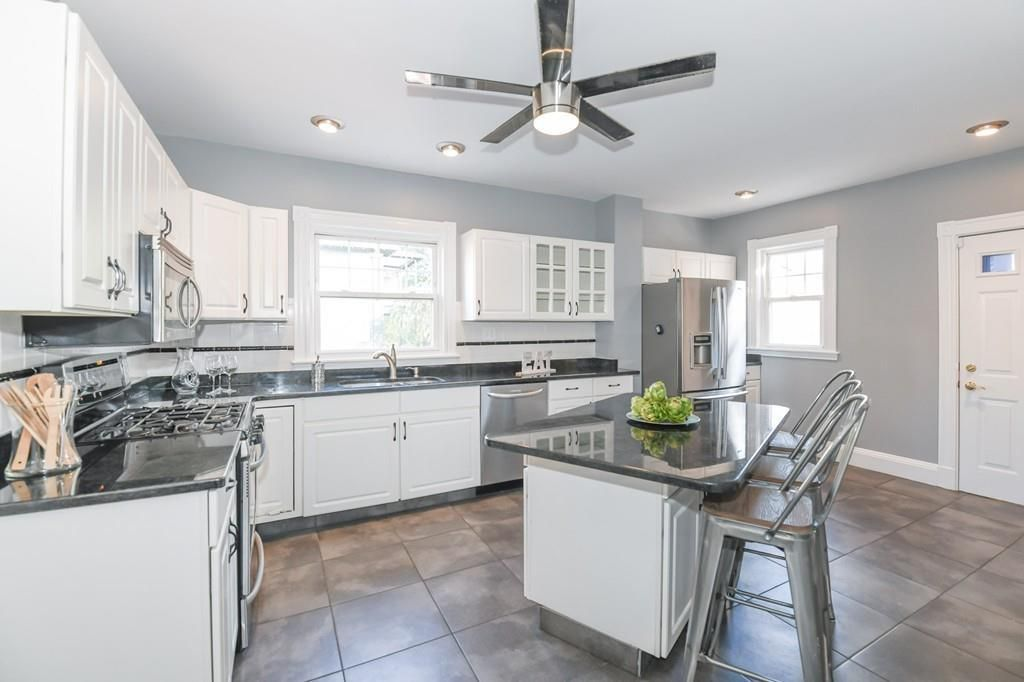 A spacious kitchen with an island a ceiling fan.
