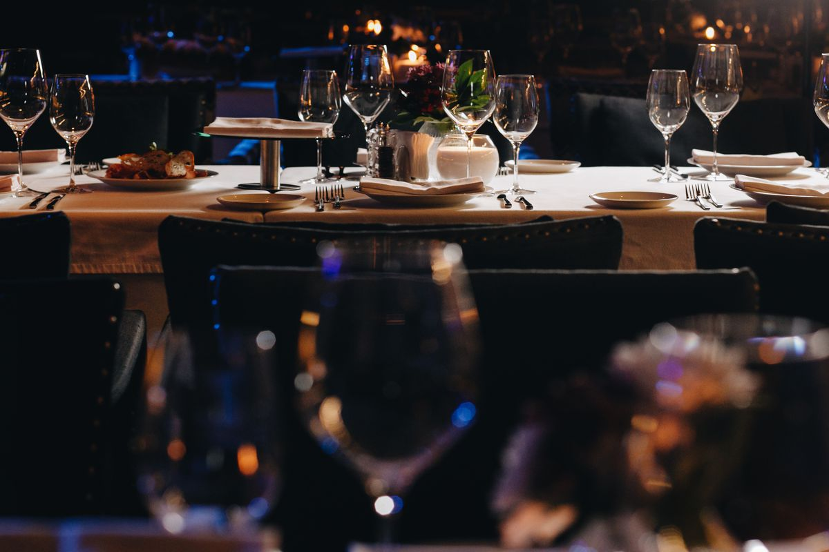 A table set inside a dimly lit restaurant, with rows of empty wine glasses