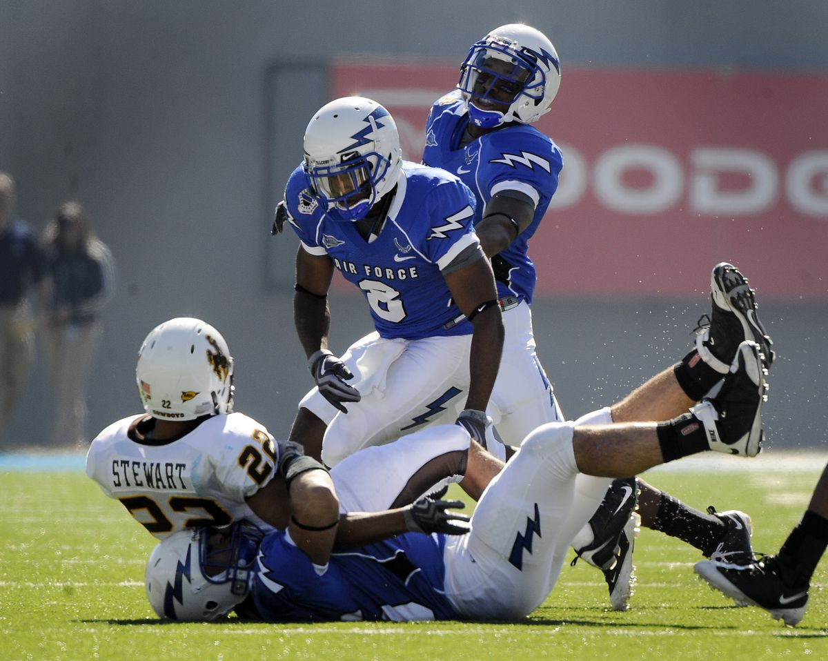 Air Force #8 Reggie Rembert watches as #45 John Falgout brings down Wyomings #22 Brandon Stewart in the 1st half of the Air Force Falcons football game against the Wyoming Cowboys at the Air Force Academy in Colorado Springs, CO. (Craig F. Walker / The De