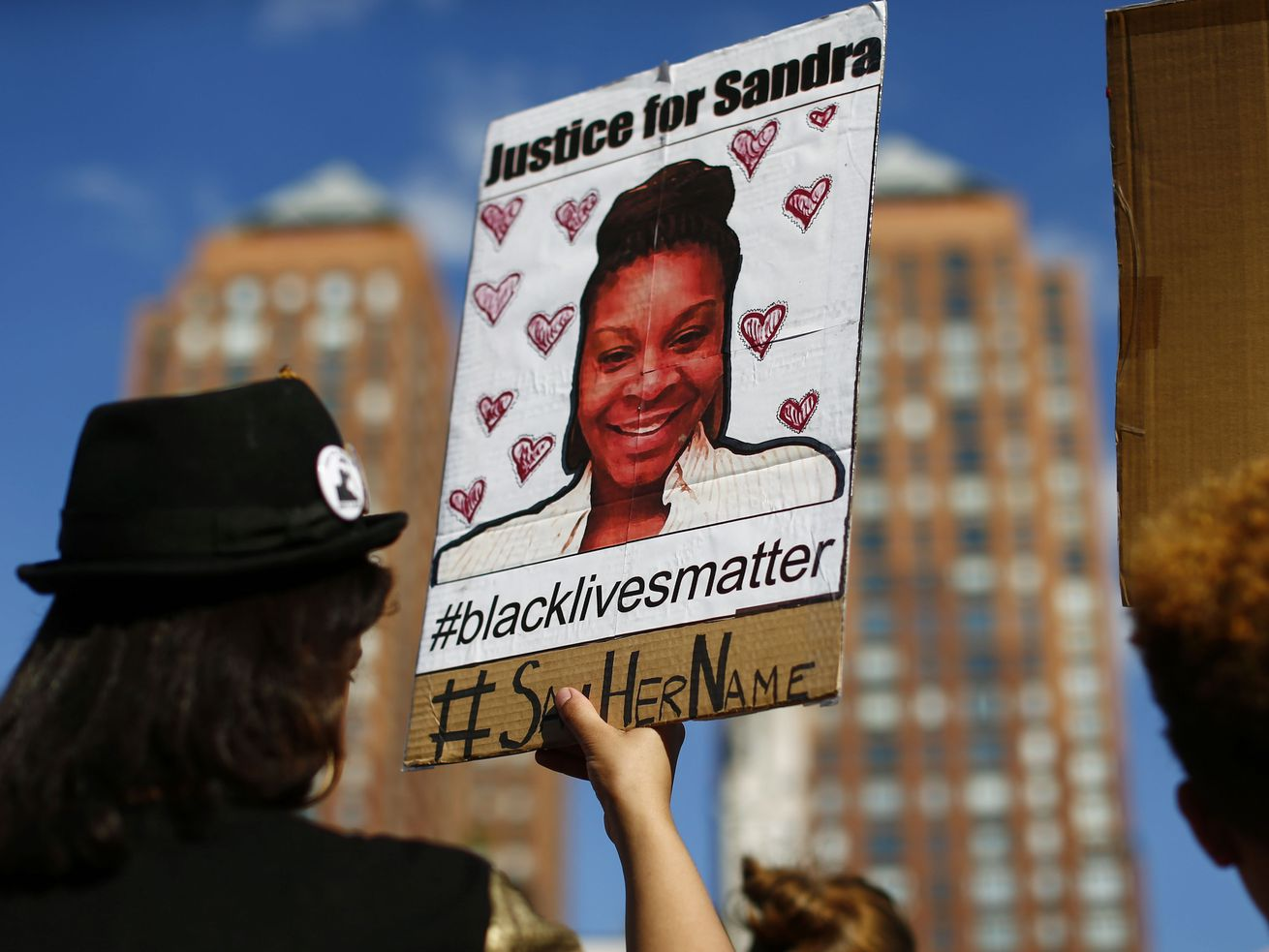 A protester carries a poster honoring Sandra Bland during a memorial rally in 2015. Nearly four years after Bland's death, her sister is speaking out in a new USA Today op-ed.