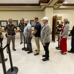People from overflow rooms line up to express their opinions about the Biden administration's COVID-19 vaccine mandate during a meeting of the Legislature's Business and Labor Interim Committee at the Capitol in Salt Lake City on Monday, Oct. 4, 2021.
