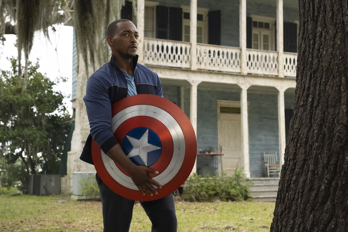 Falcon stands with the Captain America shield in front of a Louisiana mansion