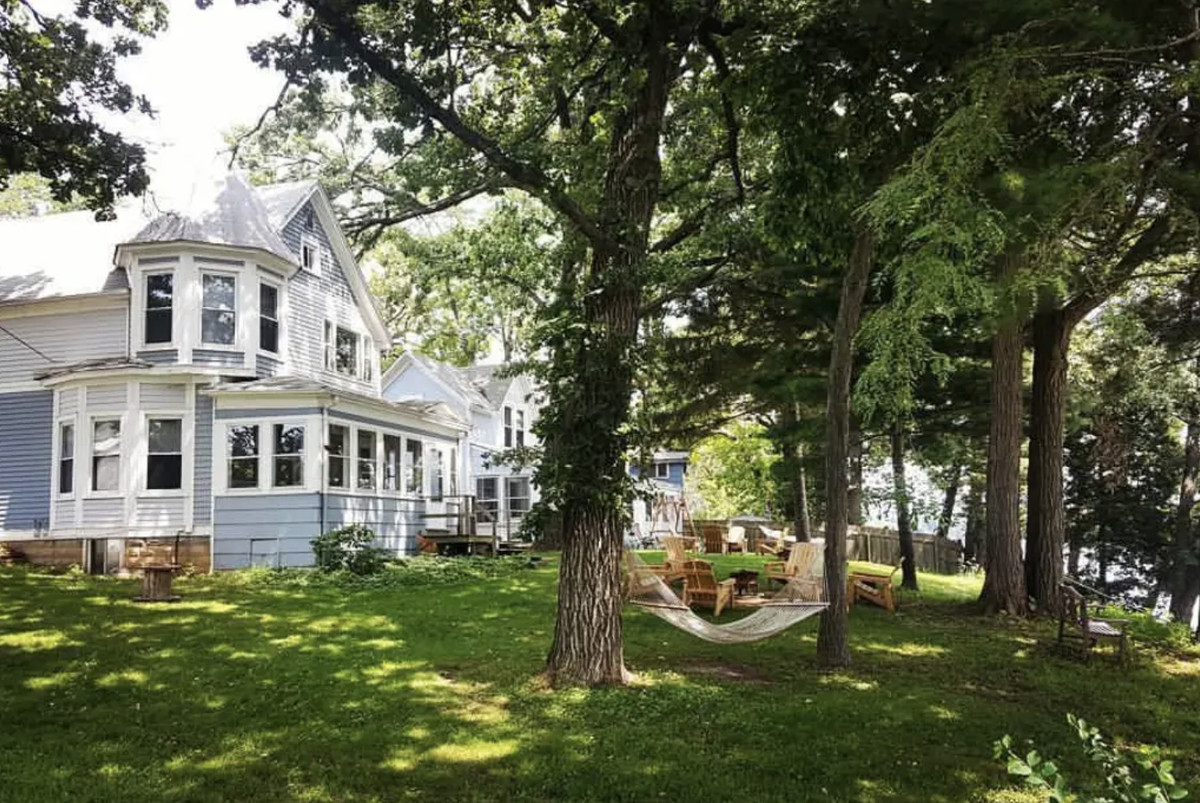 Tall trees shade a grassy backyard with Adirondack chairs, firepits, and a woven hammock. A grand two-story white and sky blue house overlooks the lake.