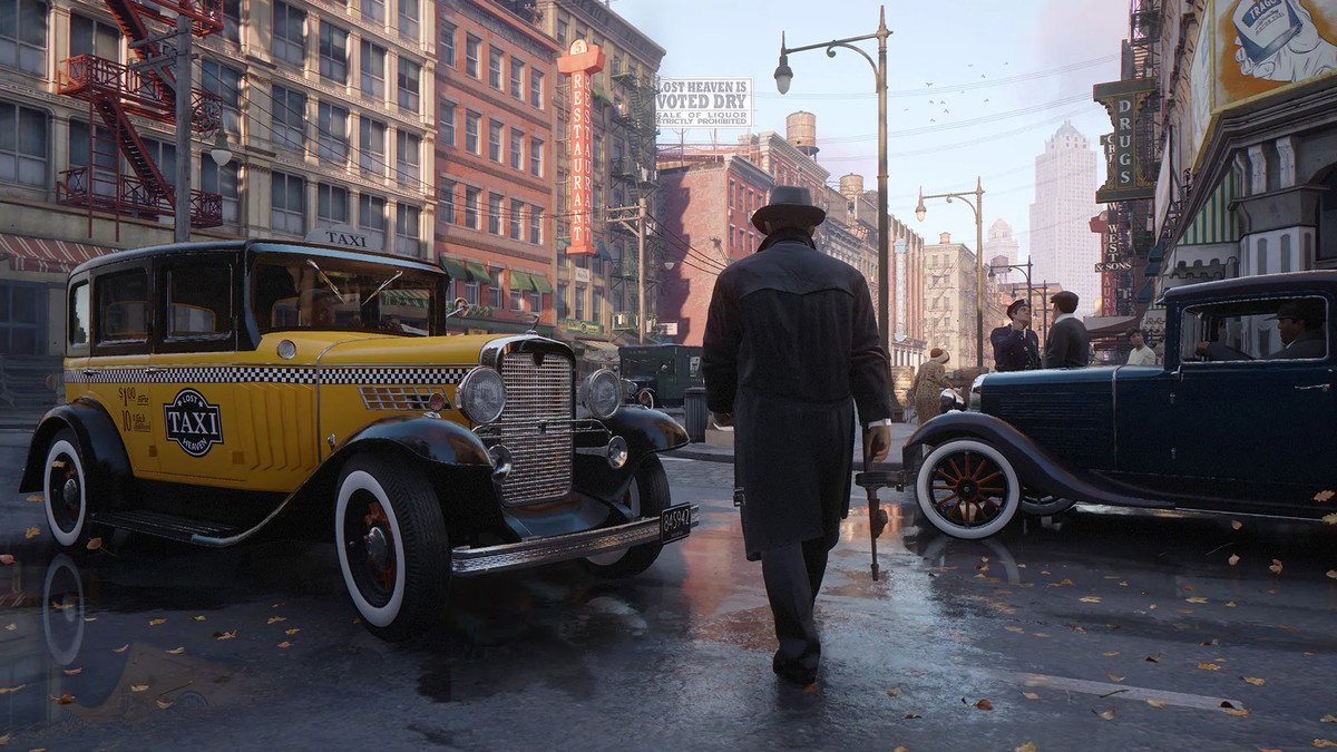 A man with a gun walks between two classic cars