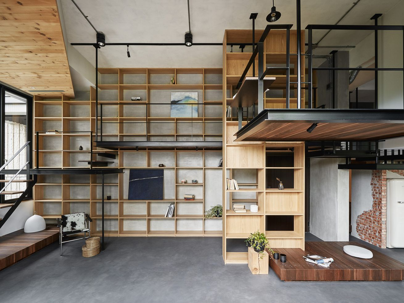 Interior of house with wooden platforms for second-floor circulation and built-in shelving on the back wall.