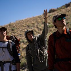 Hawkwatch International research associate Dustin Maloney, center, and field biologists Max Carlin, left, and Jayden Skelly, right, talk about the approach to a golden eagle nest on Antelope Island on Wednesday, May 19, 2021.
