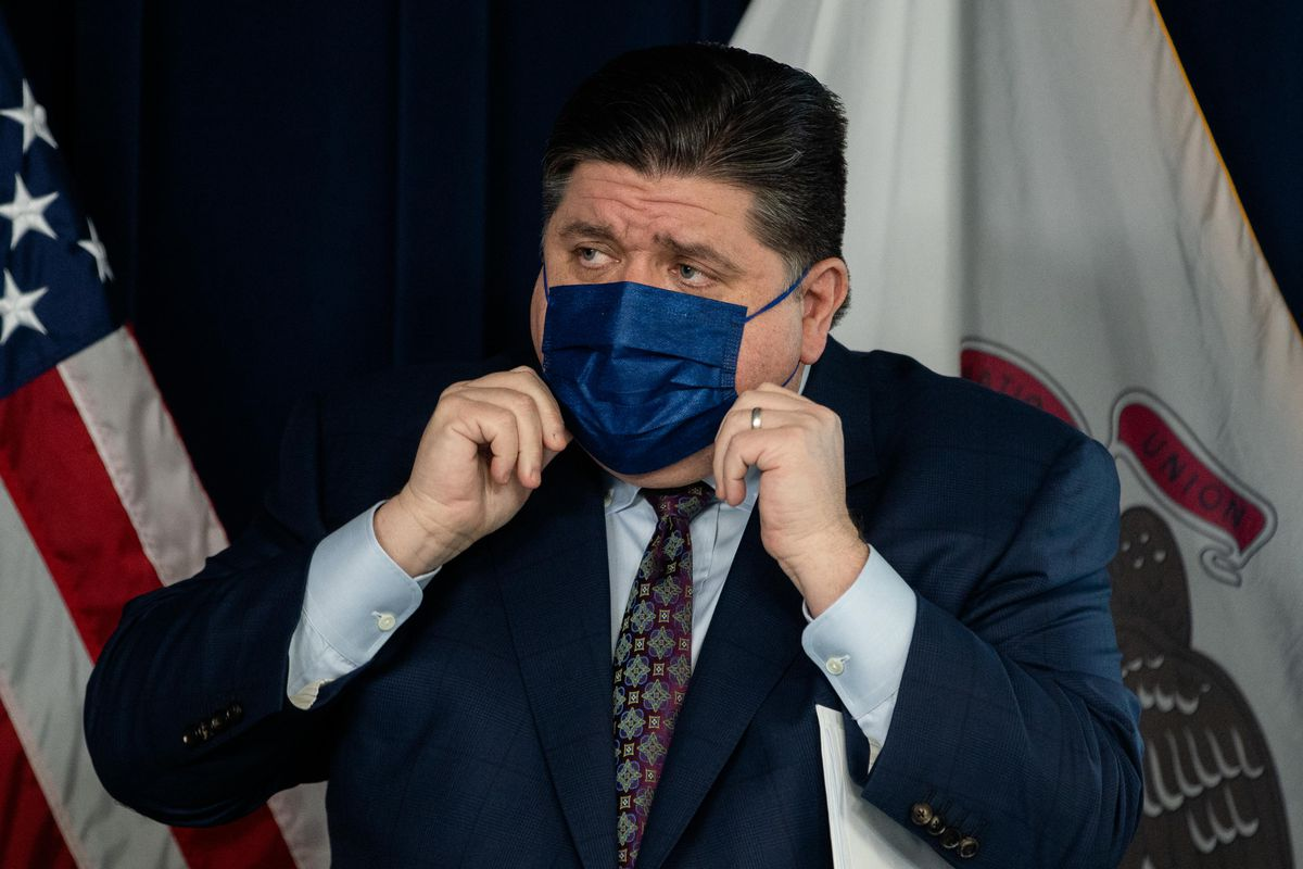 Gov. J.B. Pritzker puts on his mask during a news conference at the James R. Thompson Center in January.