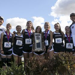 Members of the Morgan High School girls cross-country team poses with their state championship trophy after winning the 3A State Cross-Country Championships at Highland High School in Salt Lake City on Wednesday, Oct. 23, 2019.