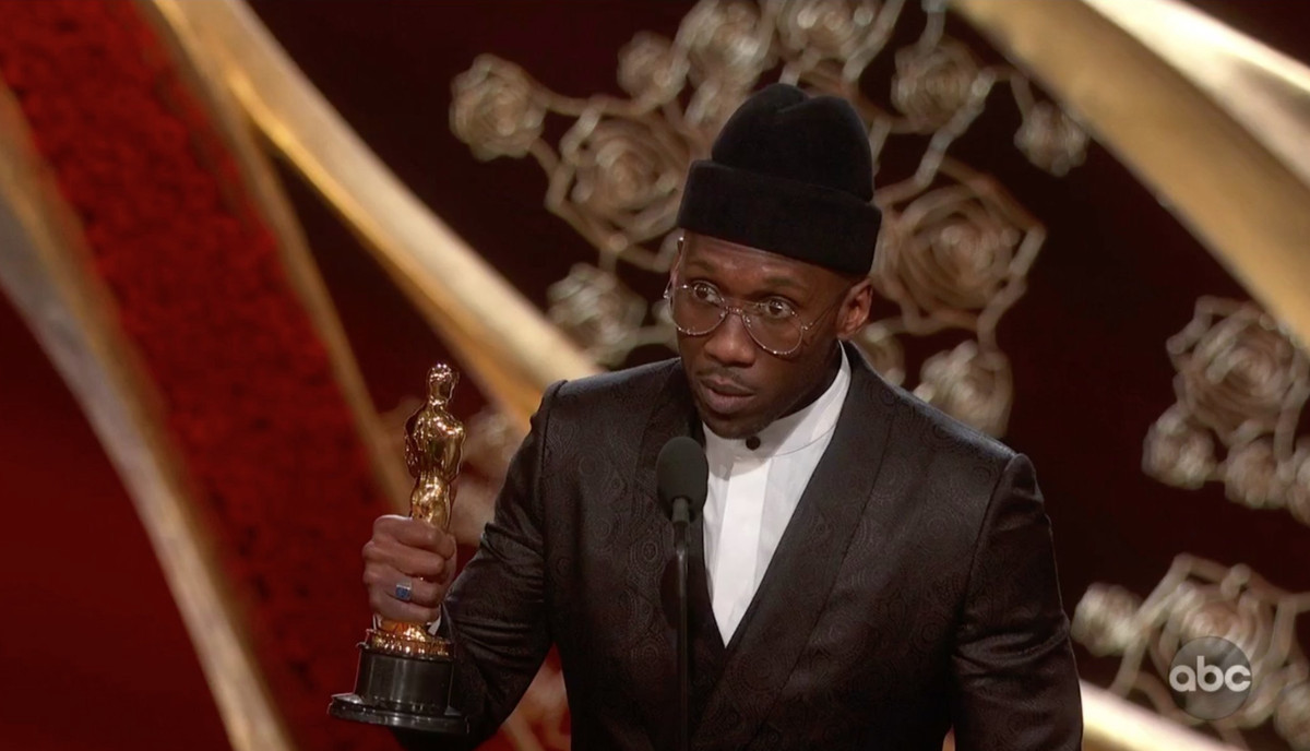 Mahershala Ali holding an Oscar trophy while wearing a black beanie with his suit