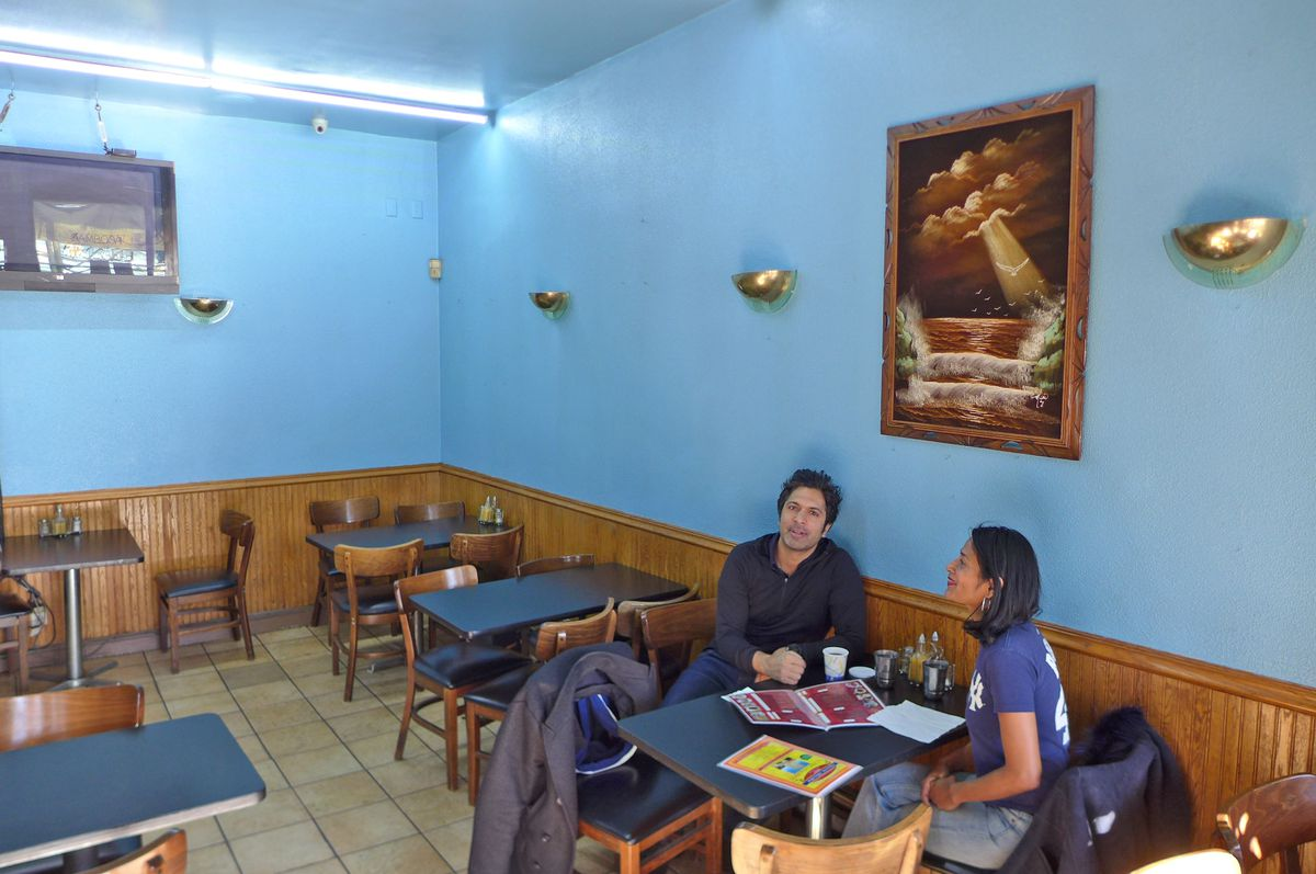 A blue walled room with several tables and a painting or two. One couple sits in the foreground.