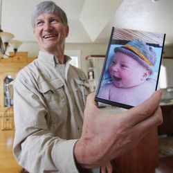 Veldon Sorensen holds a photo of one of his grandsons at his home in Salt Lake City on Sept. 13. Sorensen is retired from Bayer but still consults for the company and others about bees.