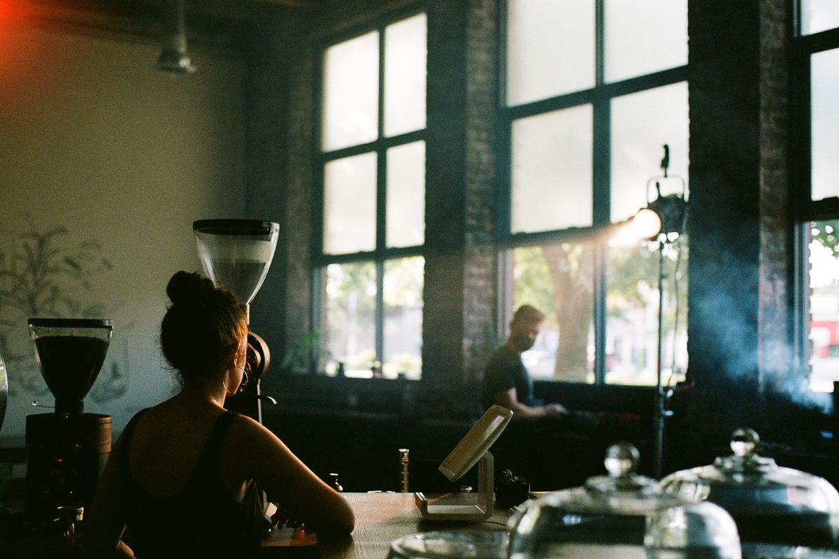 A barista in a tank top stands behind the counter at Gathering Coffee Co. looking out towards the windows where a man wearing a black face mask is standing.
