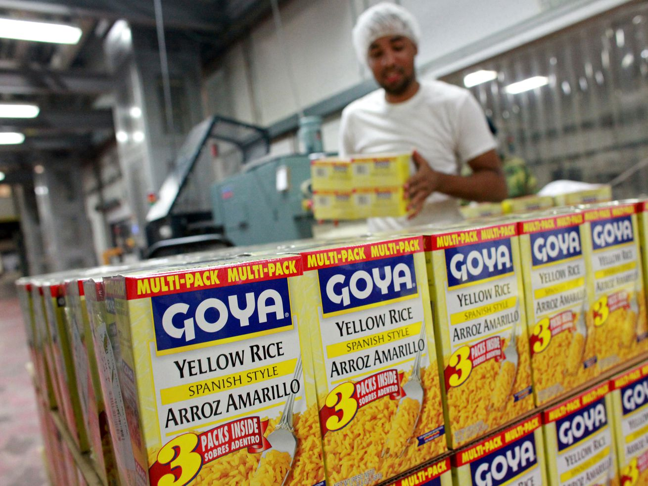 """A Black man in a hair net stacks yellow and blue boxes of Goya's """"Spanish Style"""" yellow rice on a pallet."""