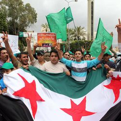 Supporters of an Islamic group and Lebanon's Future Movement of former Prime Minister Saad Hariri, wave their party flags and a giant Syrian revolution flag, and shout slogans as they march during a demonstration against the Syrian regime and to show their solidarity with the Syrian people, after Friday prayers, in Beirut, Lebanon, Friday, April 20, 2012. Syrian troops shelled a rebel-held neighborhood and sent reinforcements to border areas as the opposition called for fresh protests Friday after the United Nations accused Syrian President Bashar Assad of failing to honor a peace plan that went into effect a week ago.