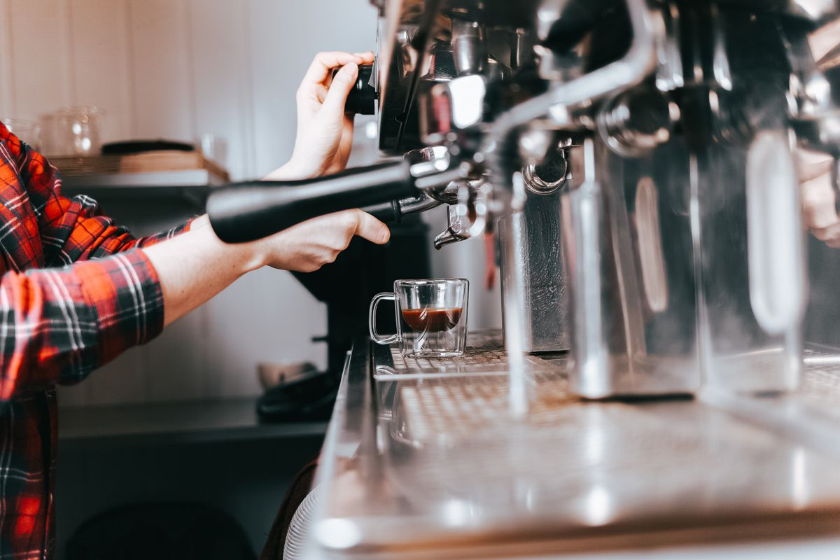 Barista makes aromatic coffee. Process of making latte on a coffee machine in a cafe