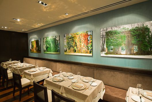 Ai Fiori's dining room has white tableclothes, a blue wall, and large photos of buildings with greenery