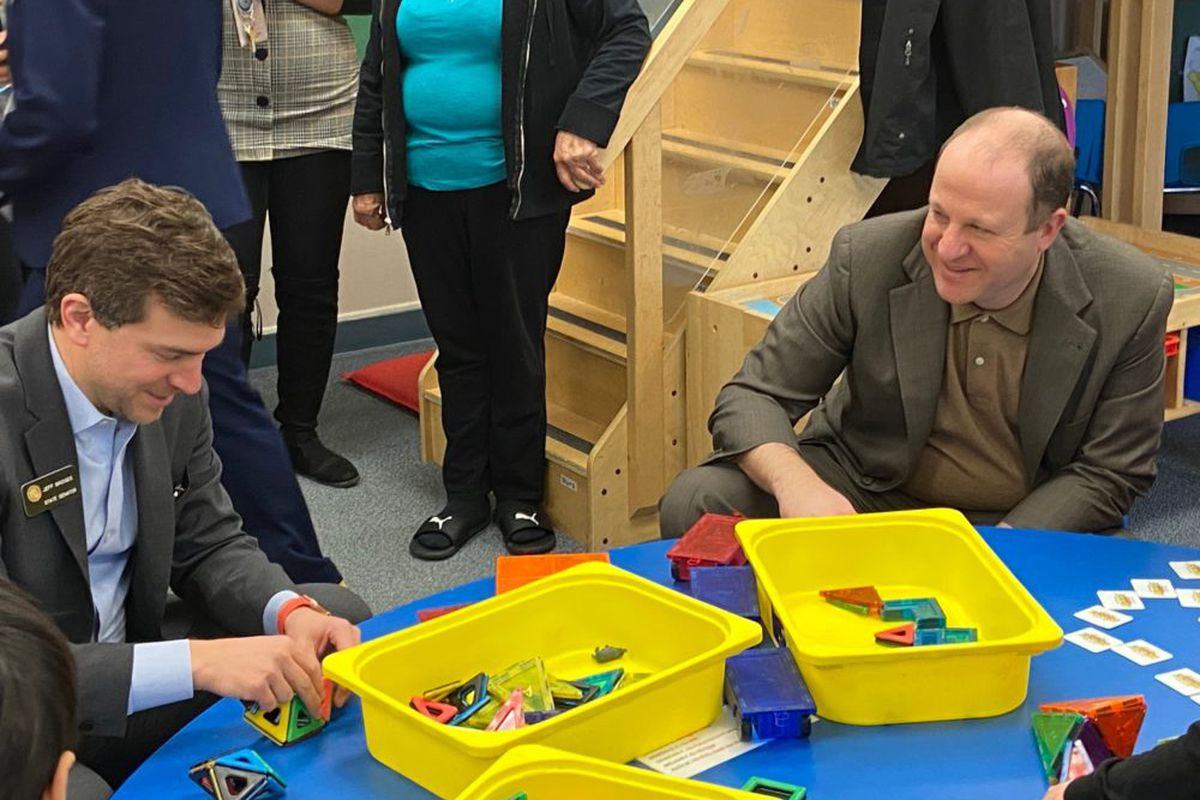 State Sen. Jeff Bridges and Gov. Jared Polis play with geometric tiles on a visit to Village for Early Childhood Education at North.