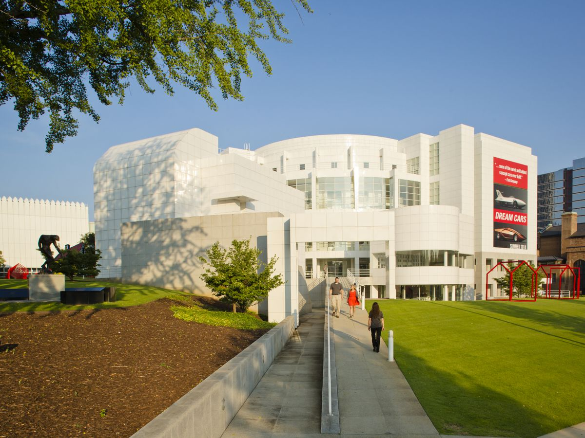 A white modernistic building is set on a big lawn.