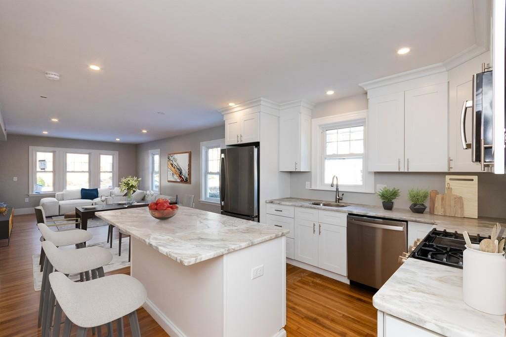 An open kitchen-living room area with a large kitchen island featuring prominently.