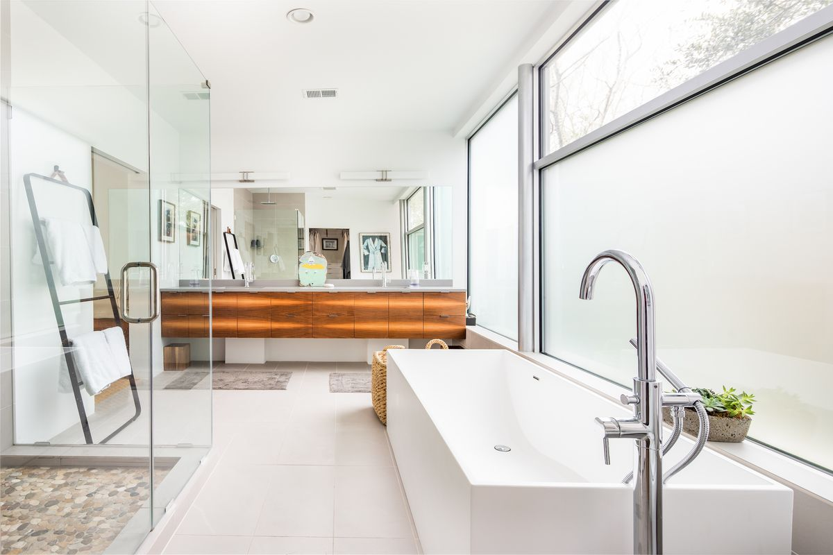 A large bathroom features a stand-up shower, soaking tub, and two sinks.
