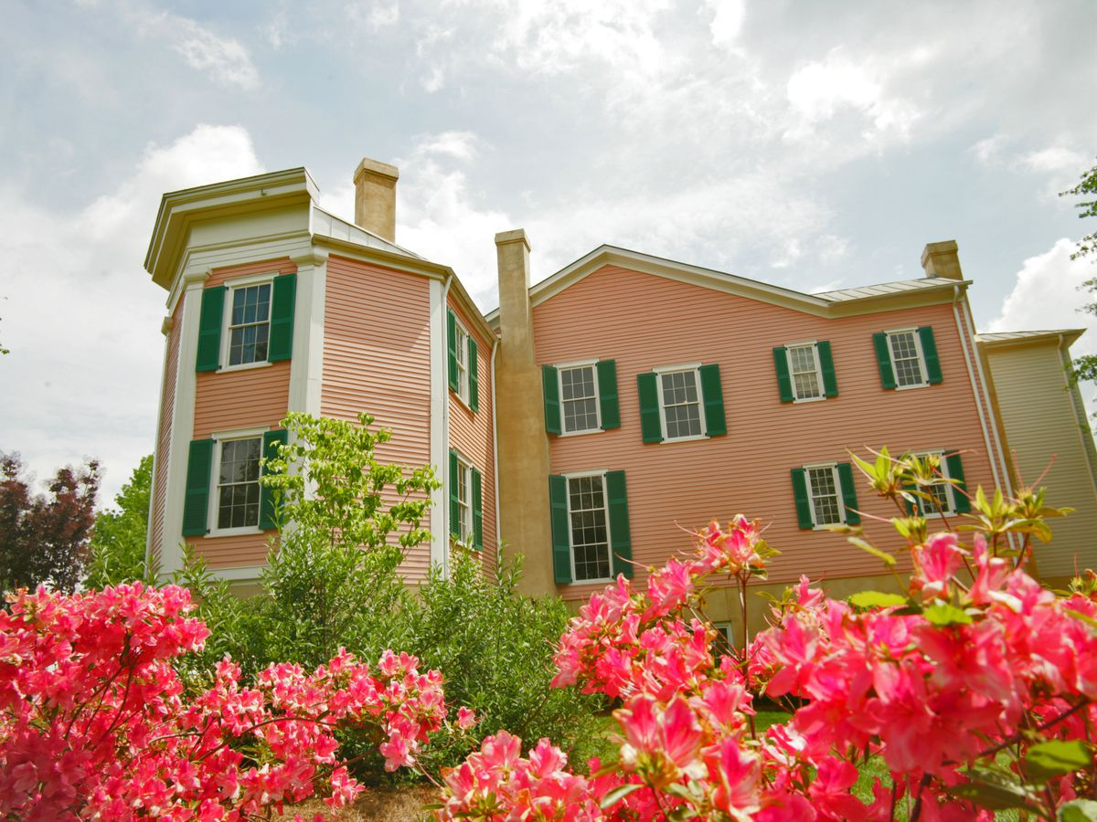 Two-story home with salmon-colored exterior and green shutters.