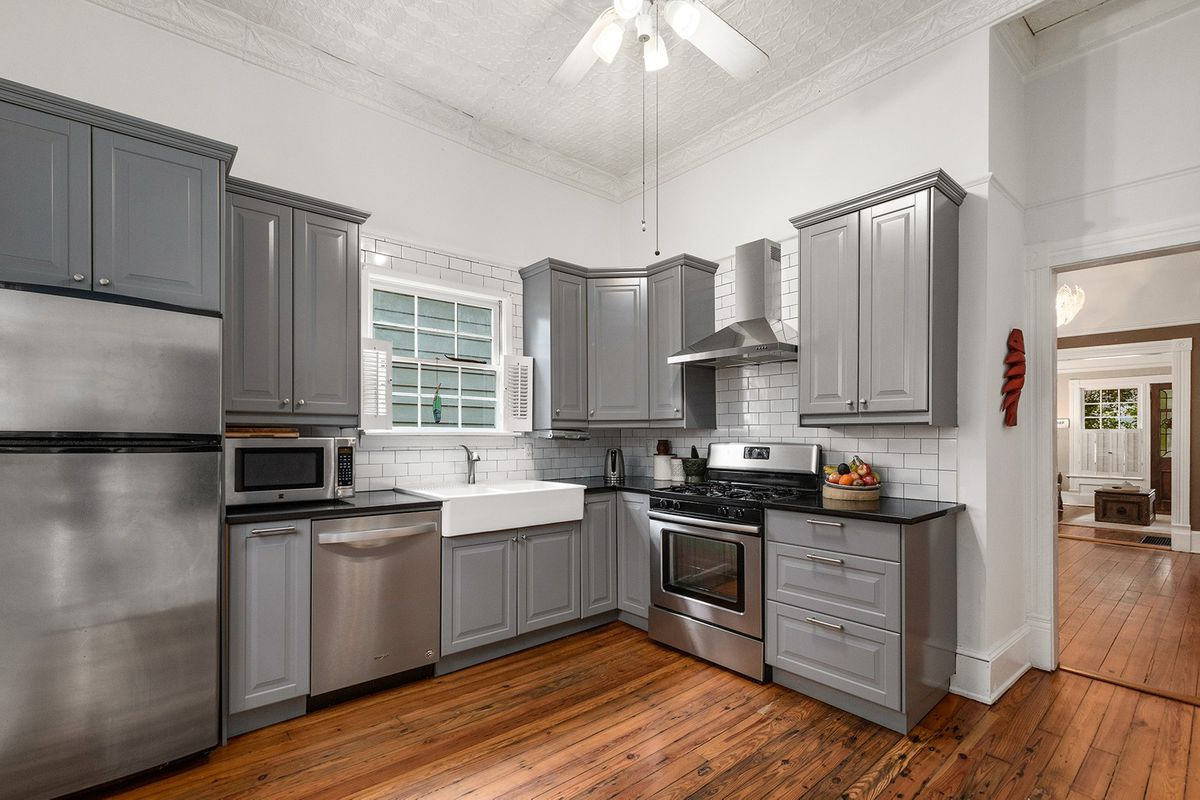 A kitchen with gray cabinets and white ceiling fan and walls.