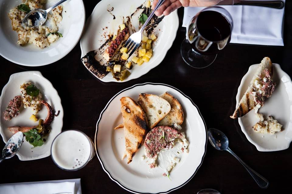 A table filled with bruchetta, mussels, and other snacks on white plates, shot from above