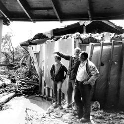 Brent Madsen and his father, Ken, show Bishop Neil Fabrizio their Bountiful home. The home was split by a wall of water and mud.