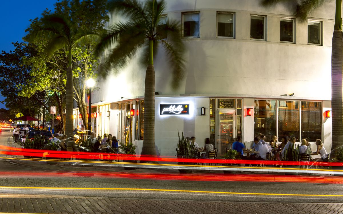 White building with palm trees and red lights in the foreground