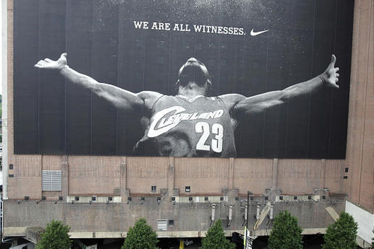 A lone passerby looks up at the giant banner of Cavaliers basketball star LeBron James on Friday, July 9, 2010, in Cleveland, Ohio, the day after James  announced that he would be signing a contract for the upcoming season to join the Miami Heat.