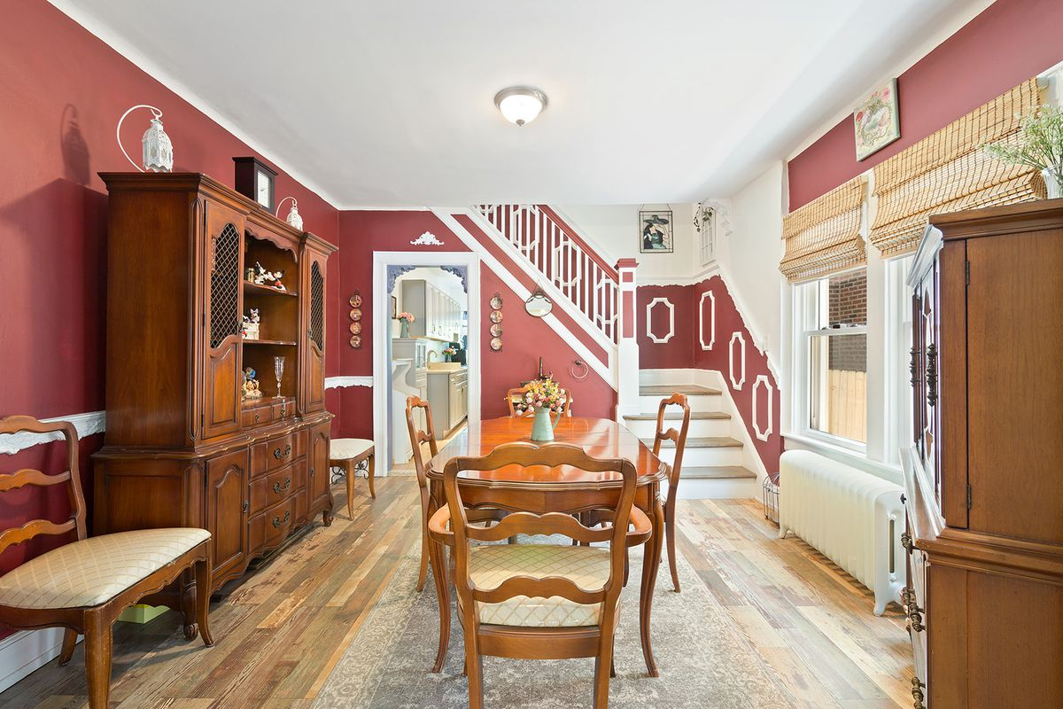 A living area with hardwood floors, two windows, wooden furniture, red walls, and a staircase in the back.
