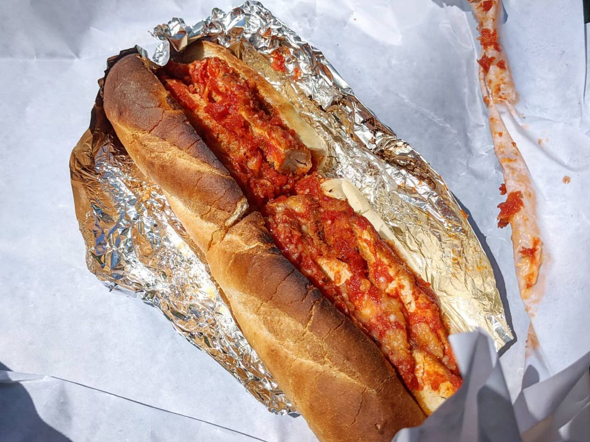 Overhead view of a chicken parm sub on a toasted roll. It's served on white paper, messy with tomato sauce.
