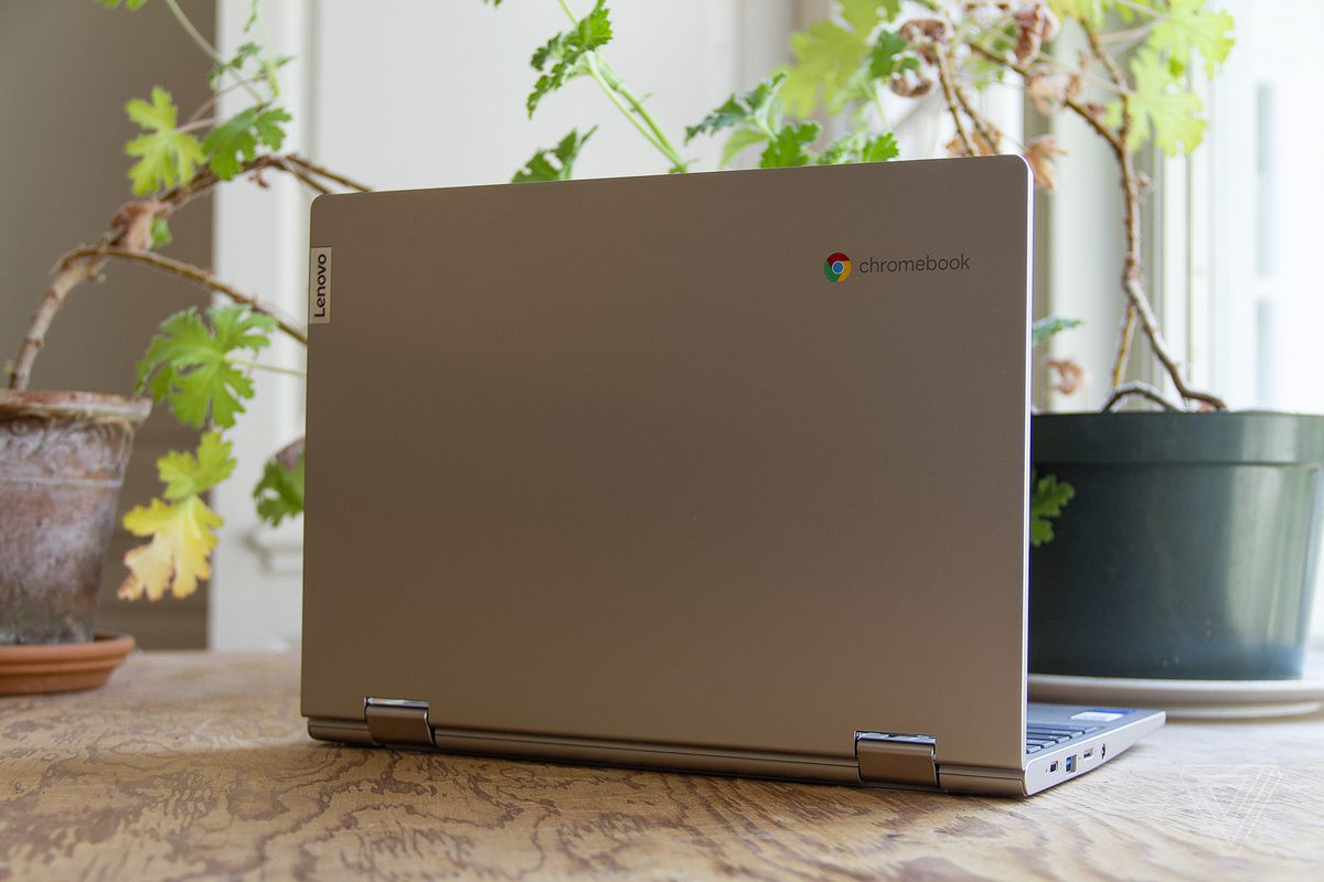 The Lenovo Ideapad Flex 3 Chromebook open, seen from the back, angled slightly to the right, on a table in front of two houseplants.