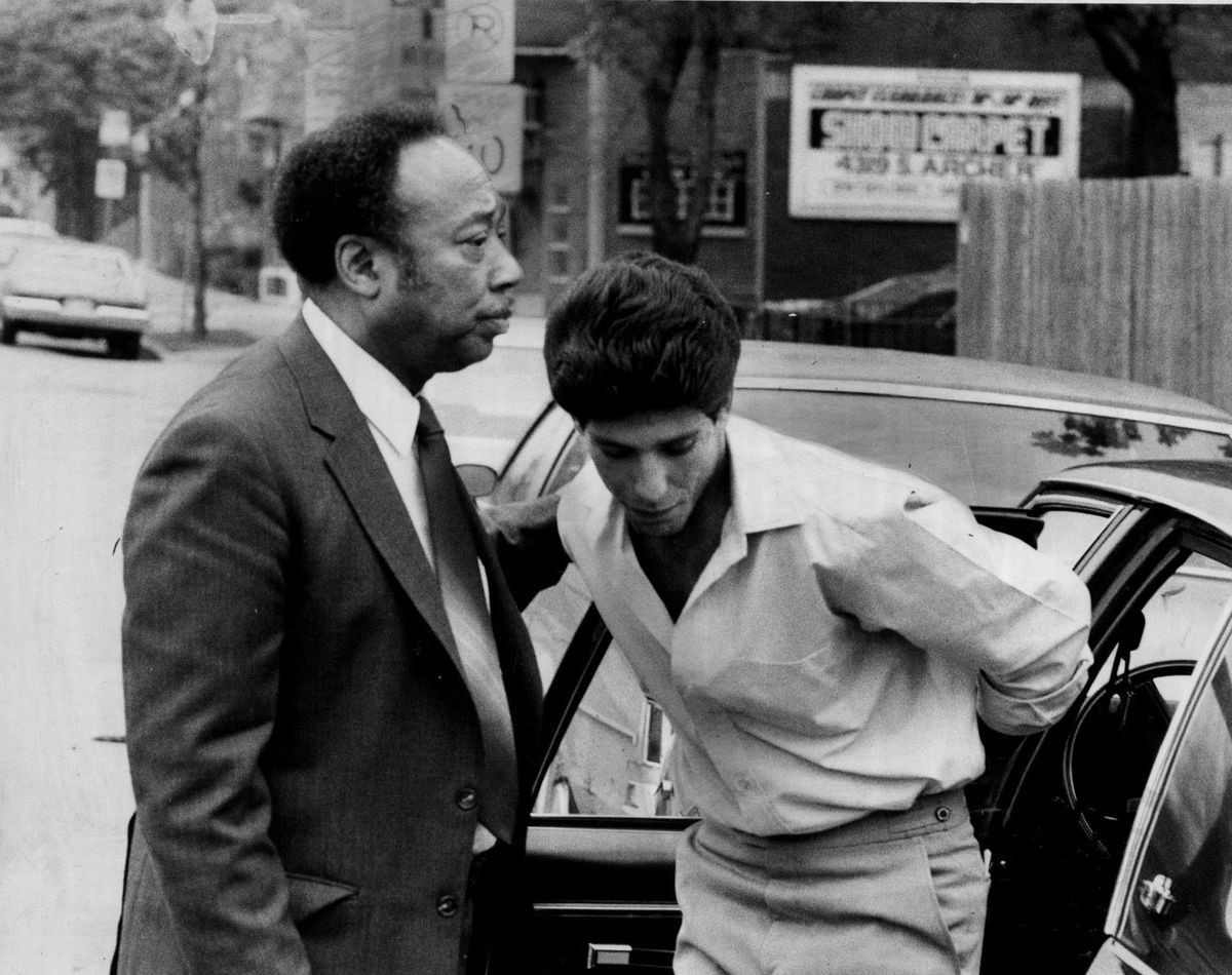 Russ Ewing accompanying murder suspect Mark Morando as he surrendered to police in 1984.