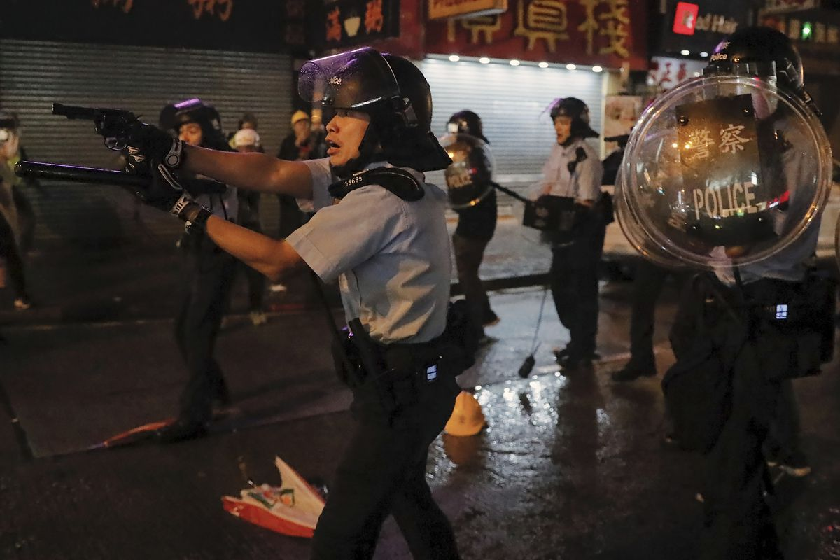 Flanked by other officers in riot gear, a police officer extends their service revolver towards protesters.