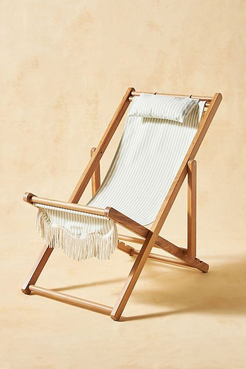 Wooden folding chair with fringed off-white seat.