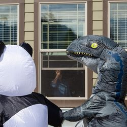 A resident of Spring Gardens Assisted Living in Holladay waves as Mary Johnson and Ryan Taggart, volunteers with Bristol Hospice Utah, parade outside the facility while wearing inflatable costumes on Saturday, April 18, 2020.