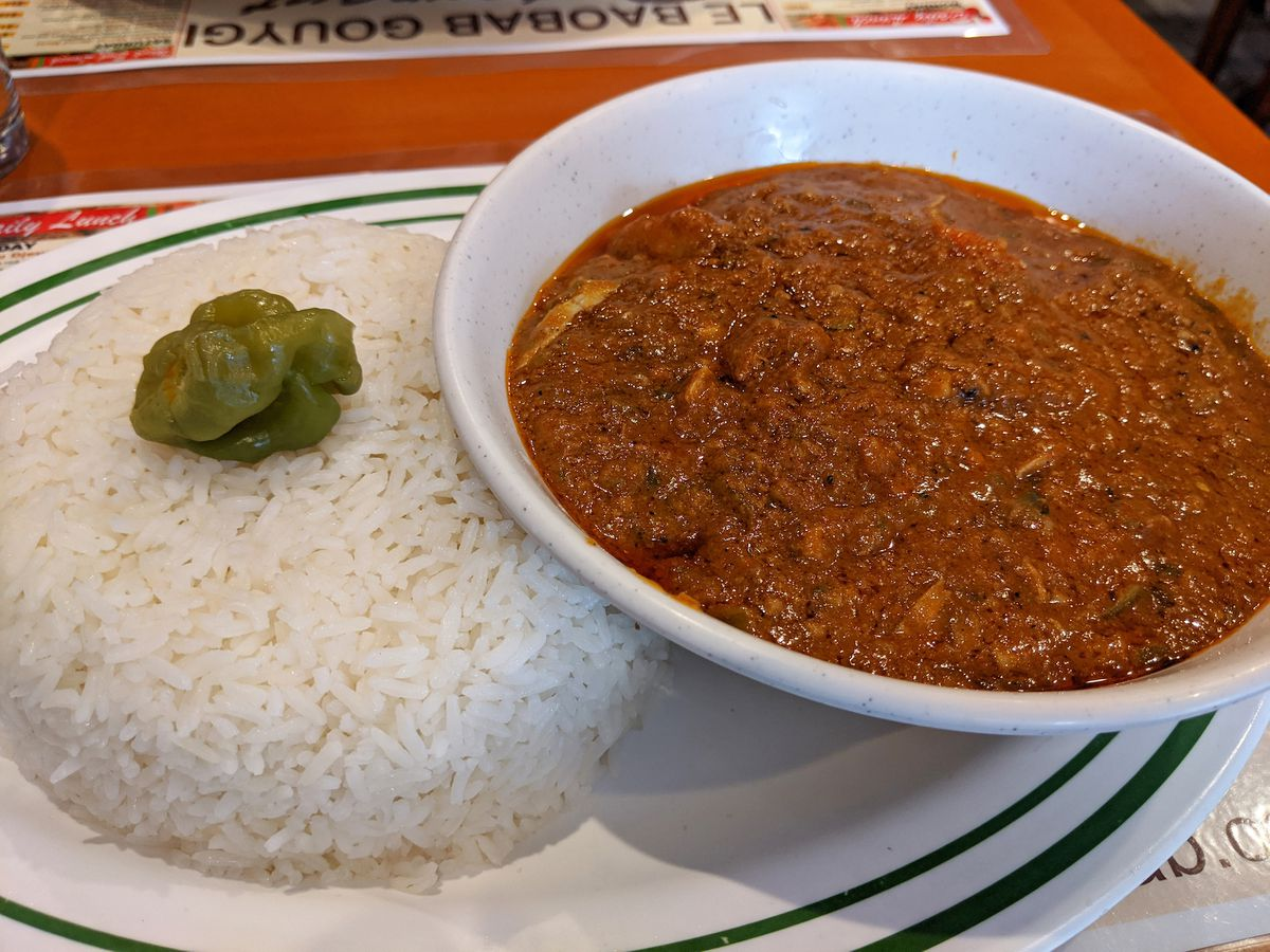 A white place with a mound of white rice on one side and a bowl with a brown chili-like dish.
