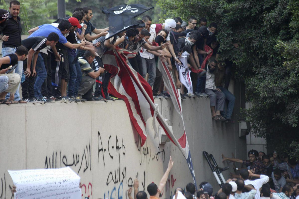 Protesters destroy an American flag pulled down from the U.S. embassy in Cairo, Egypt, Tuesday, Sept. 11, 2012. Egyptian protesters, largely ultra conservative Islamists, have climbed the walls of the U.S. embassy in Cairo, went into the courtyard and bro