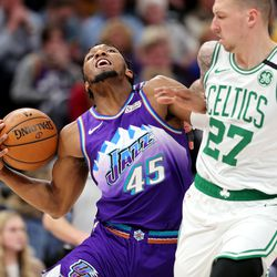 Utah Jazz guard Donovan Mitchell (45) tries to draw a foul on Boston Celtics center Daniel Theis (27) as the Utah Jazz and the Boston Celtics play an NBA basketball game at Vivint Smart Home Arena in Salt Lake City on Wednesday, Feb. 26, 2020. Boston won 114-103.