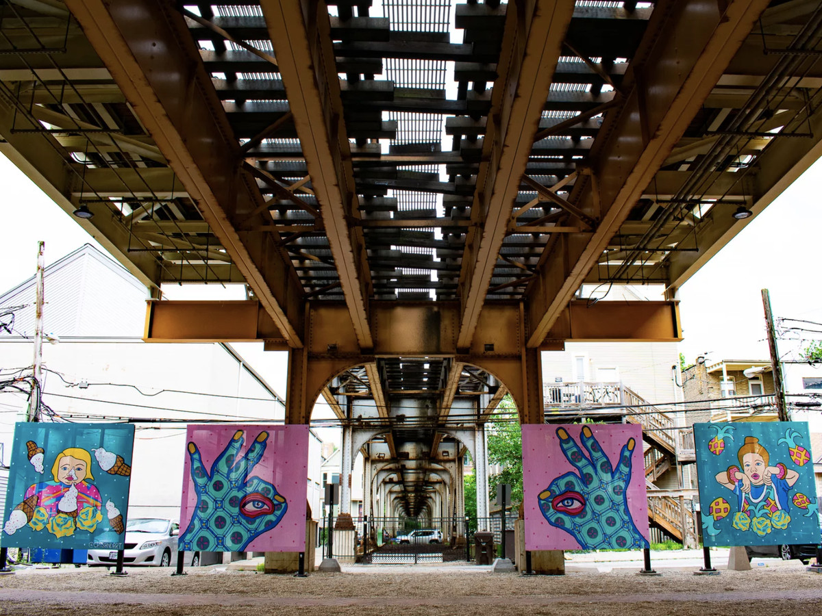 Various colorful murals under elevated train tracks.