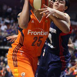 Connecticut Sun's Alyssa Thomas (25) is fouled by Washington Mystics' Bria Hartley (8).