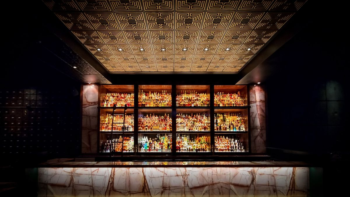 A large pink marble bar backed by shelves of bottles.