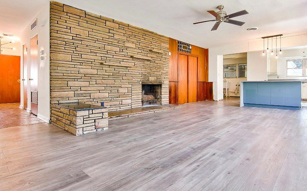 A large living room with stone and wood walls.