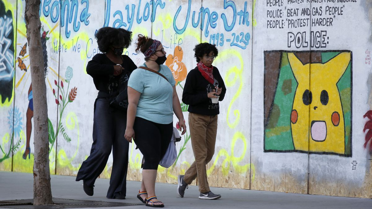 """Three women walking on a sidewalk, a mural next to them reads""""Breonna Taylor June 5th"""" and there's a painting of Pikachu next to it."""