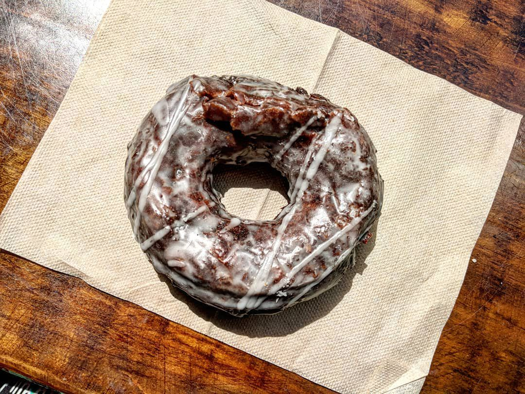 Overhead view of a glazed chocolate donut on a brown paper napkin on a wooden surface