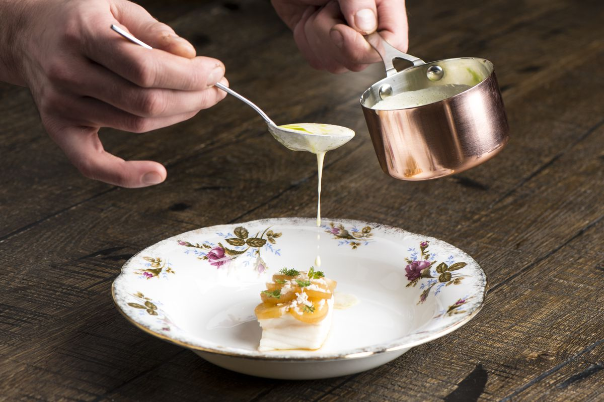 A chef pours a white sauce over a fish dish
